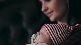 Moeder die pasgeboren baby kussen dichtbij Kerstboomclose-up stock footage