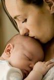 Moeder die pasgeboren baby kust Royalty-vrije Stock Afbeelding