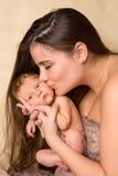 Moeder die pasgeboren baby kust Stock Fotografie