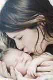 Moeder die pasgeboren baby kust Stock Afbeelding