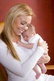 Moeder die pasgeboren baby in schommelstoel houdt Royalty-vrije Stock Foto