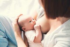 Moeder die pasgeboren baby thuis de borst geven stock fotografie