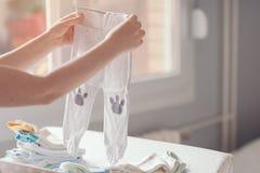 Moeder die pasgeboren babykleding thuis sorteren stock afbeeldingen