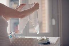 Moeder die pasgeboren babykleding thuis sorteren stock fotografie