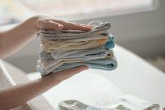 Moeder die pasgeboren babykleding thuis sorteren stock foto's