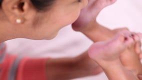 Moeder die pasgeboren babyvoeten kussen stock footage