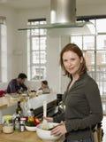 Moeder die Salade met Familiezitting voorbereiden op Achtergrond Royalty-vrije Stock Foto