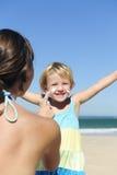Moeder die suncream op haar gelukkig kind van toepassing is Stock Afbeelding