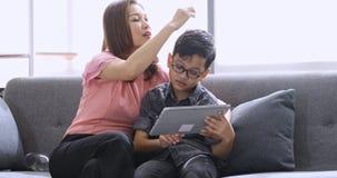Moeder die tablet met haar zoon in woonkamer gebruiken stock video