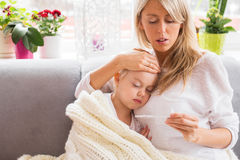Moeder die temperatuur van haar zieken controleren weinig dochter Royalty-vrije Stock Foto's