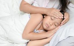 Moeder die temperatuur van ziek jong geitje meten stock foto's