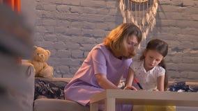 Moeder die thuiswerk met haar doen weinig dochter, ouder die jong geitje met studie, familieconcept binnen helpen stock footage