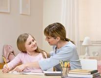 Moeder die thuiswerk verklaart aan dochter Stock Afbeeldingen