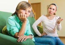 Moeder die tienerzoon berispen stock afbeeldingen