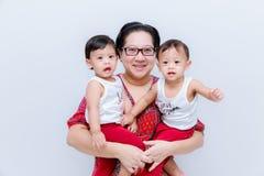 Moeder die twee babyjongens houden Groot geluk, gelukkig jong mamma met twee tweelingenbaby Portret die van jonge moeder haar hou royalty-vrije stock afbeeldingen