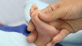 Moeder die uiterst kleine voet van pasgeboren baby houden stock footage