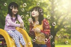 Moeder die van tijd met dochter op de speelplaats genieten Royalty-vrije Stock Foto
