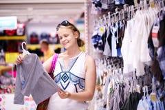 Moeder die voor de kleren van kinderen winkelen stock fotografie