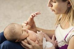 Moeder die voor kleine baby geven stock foto