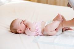 Moeder die weinig baby behandelen en luier veranderen Royalty-vrije Stock Foto