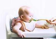 Moeder die weinig baby met lepel voeden stock foto