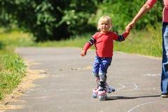 Moeder die weinig daugther helpen aan rolschaats stock afbeeldingen