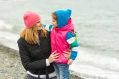 Moeder die weinig dochter koesteren en teder haar op strand in koud weer bekijken Royalty-vrije Stock Foto's