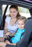 Moeder die weinig dochter vastmaken in de zetelauto van de zuigelingsveiligheid Royalty-vrije Stock Foto
