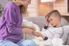 Moeder die weinig zoon behandelen die aan koude lijden Stock Afbeelding