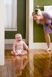 Moeder die zich naast gelukkige babyzitting bevindt op vloer stock foto's