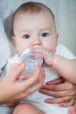 Moeder die zijn babyjongen voeden door melk van fles Stock Afbeelding
