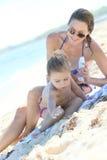 Moeder die zonbescherming op haar dochter toepassen Royalty-vrije Stock Foto