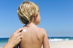 Moeder die zonnescherm op child?s terug toepast Royalty-vrije Stock Afbeeldingen