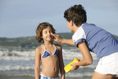 Moeder die zonnescherm toepast op dochter bij strand Stock Foto's