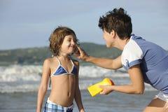 Moeder die zonnescherm toepast op dochter bij strand Royalty-vrije Stock Foto's