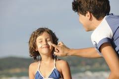 Moeder die zonnescherm toepast op dochter bij strand Stock Afbeelding