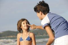 Moeder die zonnescherm toepast op dochter bij strand Stock Fotografie