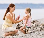 Moeder die zonnescherm toepast op dochter bij strand Stock Afbeeldingen