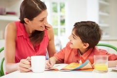 Moeder die Zoon met Thuiswerk helpen Royalty-vrije Stock Foto's