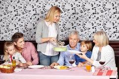Moeder dienend voedsel aan familie bij royalty-vrije stock afbeeldingen