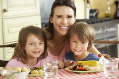 Moeder Dienende Maaltijd aan Kinderen in Keuken stock afbeeldingen