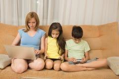 Moeder, dochter, zoon met laptop en tabletpc De Verslaving van Internet stock fotografie