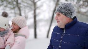 Moeder draagt dochter in een springpak op kerstvakantie in de openlucht op sneeuwdag Vrouw met een baby in roze romans stock footage