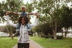 Moeder dragende jongen op schouders bij park stock afbeelding