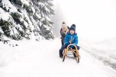 Moeder duwende zoon op slee Mistige witte de winteraard stock foto
