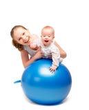 Moeder en baby die gymnastiek- oefeningen op de bal doen Stock Foto's