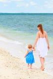 Moeder en baby die langs tropisch strand lopen Royalty-vrije Stock Foto's