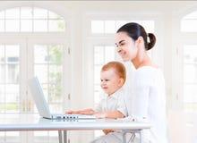 Moeder en baby die laptop met behulp van stock fotografie