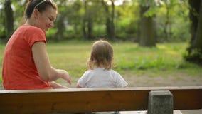 Moeder en baby die op een paardebloem op de aard in de zomer in het park blazen stock videobeelden