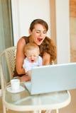 Moeder en baby die terwijl het werken aan laptop gieren Stock Foto